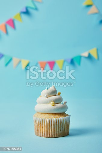 istock Delicious cupcake with sugar sprinkles on blue background with bunting 1070158934
