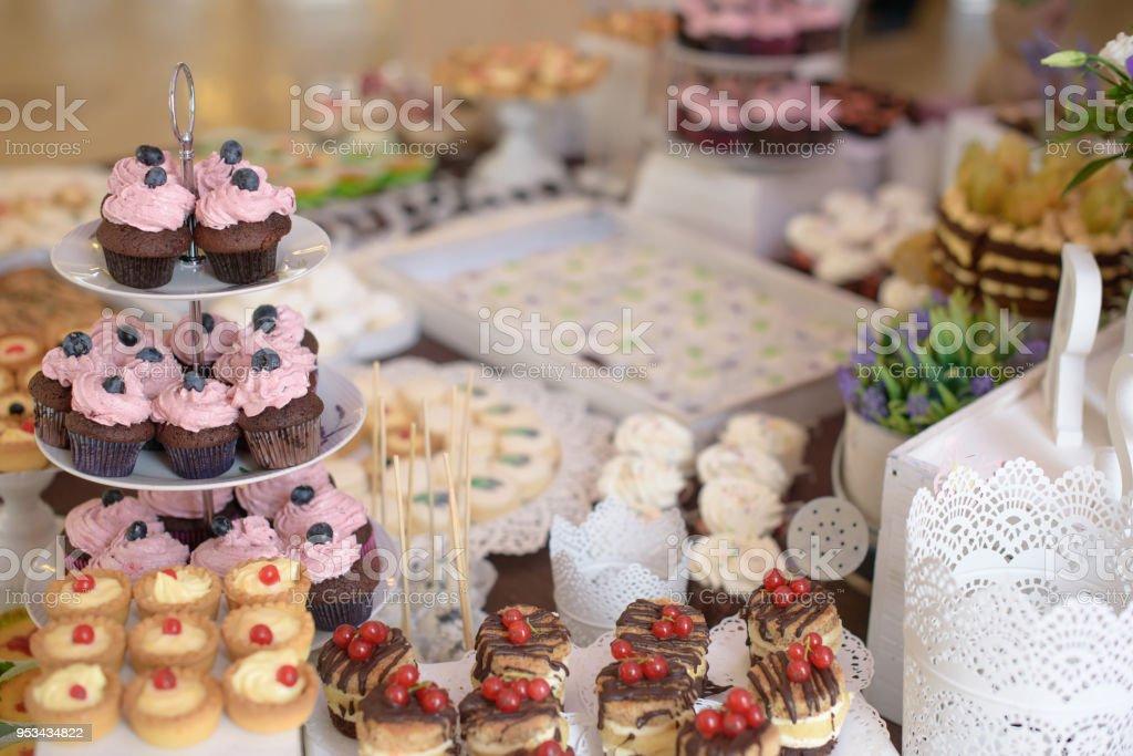 Deliciosos cupcakes con frutas del bosque en un soporte de la torta con gradas y un gran surtido de tartas y dulces - foto de stock