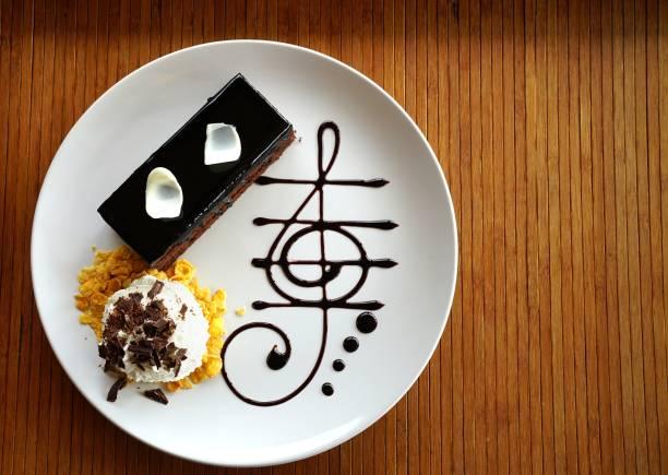 dunkle schokolade kuchen verziert mit stück weiße schokolade locken, schlagsahne und schokolade musiknote in weißer teller auf holztisch. - musik kuchen stock-fotos und bilder