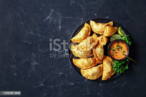 delicious deep fried Buffalo Chicken Empanadas with Low Calorie Dip on a black platter on a concrete table, horizontal view from above, flat lay, free space