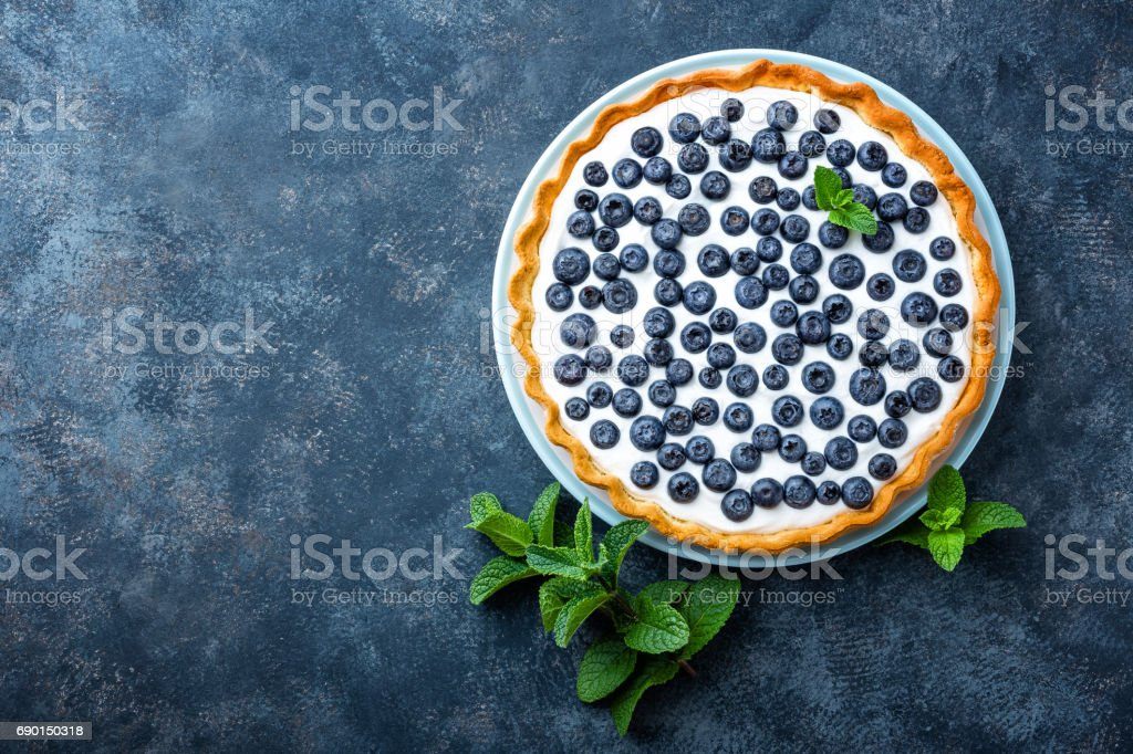 Delicious dessert blueberry tart with fresh berries and whipped cream, sweet tasty cheesecake, berry pie. French cuisine stock photo