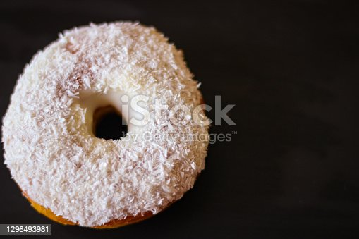 Delicious Donuts with coconut shavings on a black background