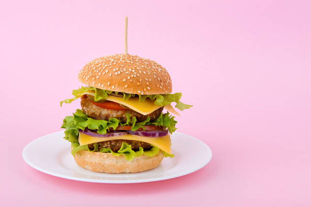 Delicious double cheeseburger on a plate on pink background