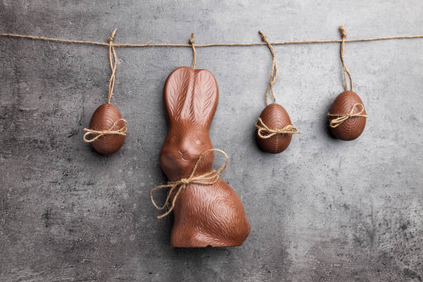 delicious easter chocolate bunny and eggs hanging on a string - easter bunny stock photos and pictures