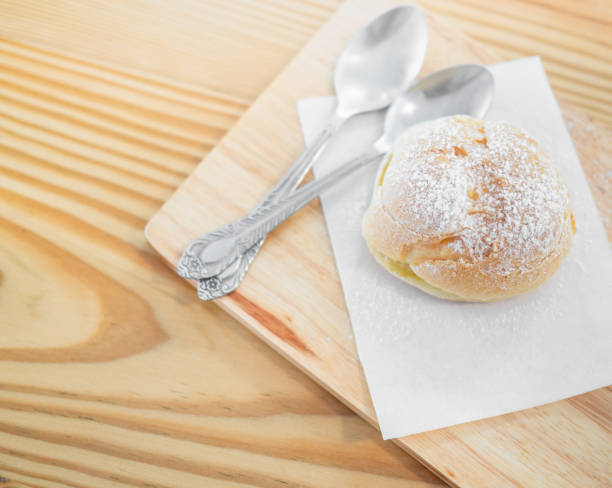 Delicious eclairs sprinkled with icing sugar Delicious eclairs sprinkled with icing sugar and spoons on wooden cutting board on table. blotting paper stock pictures, royalty-free photos & images