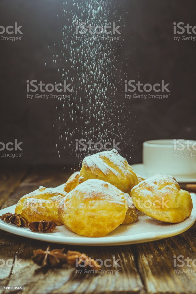 Delicious eclairs sprinkled with icing sugar, stand on a wooden table. Copy spase. stock photo