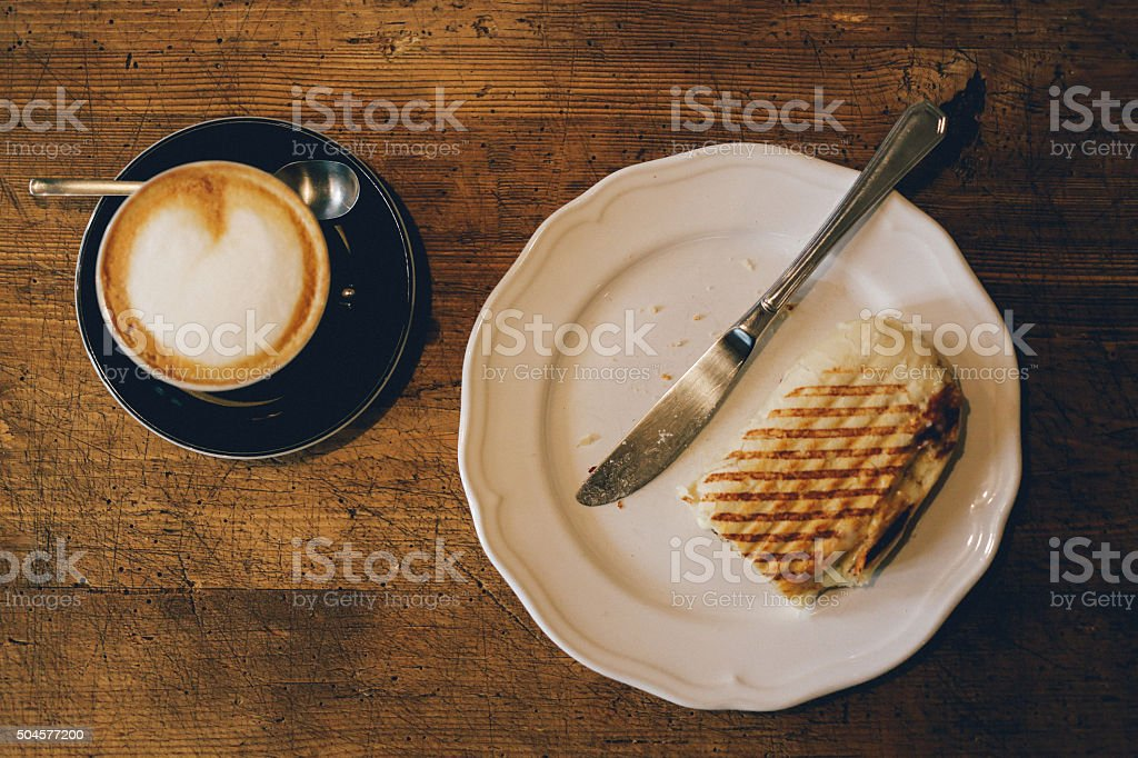 Delicious espresso and a sandwich on the wooden table stock photo