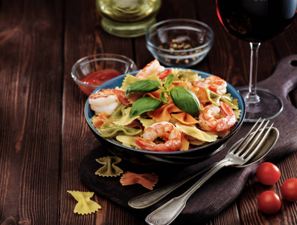 Cтоковое фото Delicious farfalle pasta with shrimps on wooden background. Mediterranean cuisine