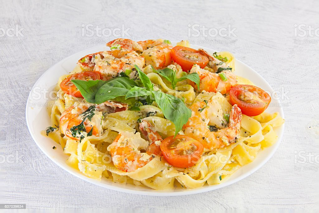 delicious fettuccine pasta with prawns on white plate stock photo