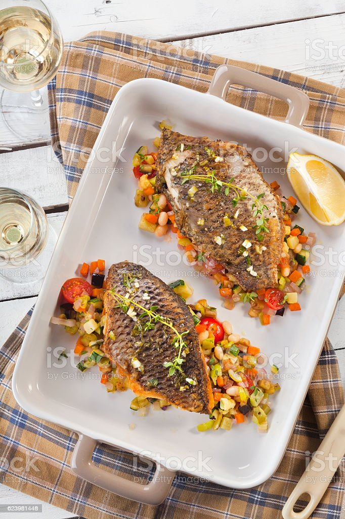 delicious fishes baked with vegetables and spices stock photo