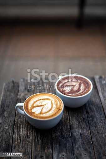 Delicious flat white coffee and hot chocolate with froth art on top of wooden table