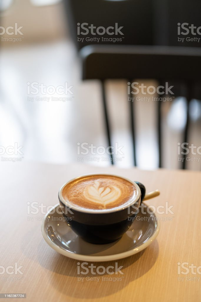 Delicious flat white coffee with coffee art on top of wooden table