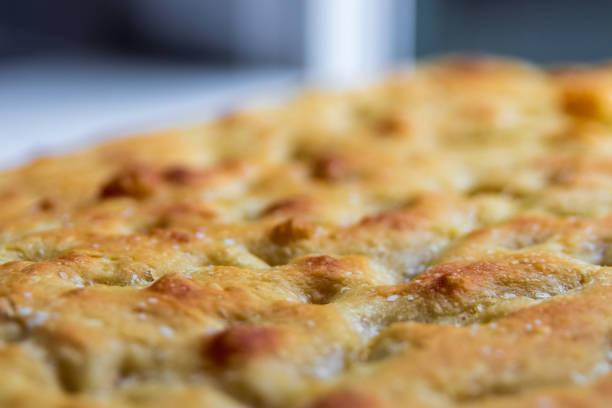 Delicious focaccia bread seasoned with salt macro close up stock photo