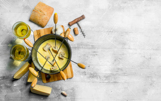 leckerer fondue-käse mit brot und weißwein - fondue stock-fotos und bilder