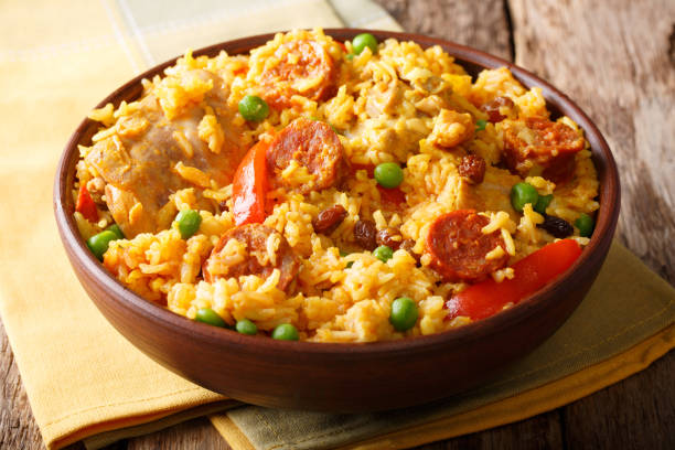 Delicious food: Arroz Valenciana with rice, meat, sausage, raisins and vegetables close-up in a bowl. horizontal Delicious food: Arroz Valenciana with rice, meat, sausage, raisins and vegetables close-up in a bowl on the table. horizontal arroz stock pictures, royalty-free photos & images