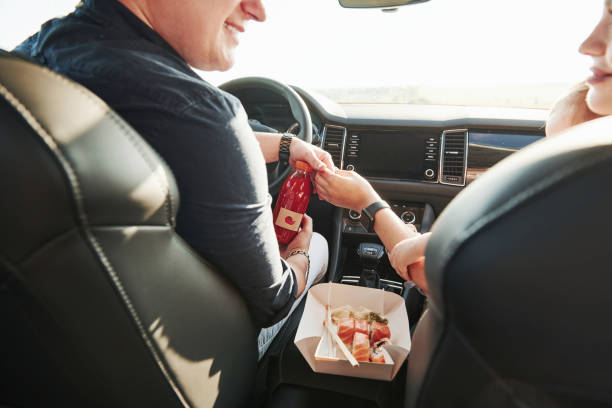 Delicious food. Beautiful people is in the modern car at their weekends stock photo