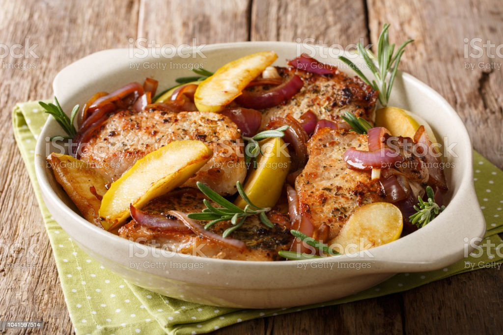 Delicious food: pork chop with green apples, onions and rosemary close-up. horizontal stock photo