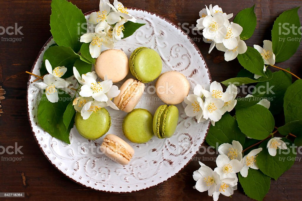 Delicious french macarons on dish   on  wooden table. Top view stock photo