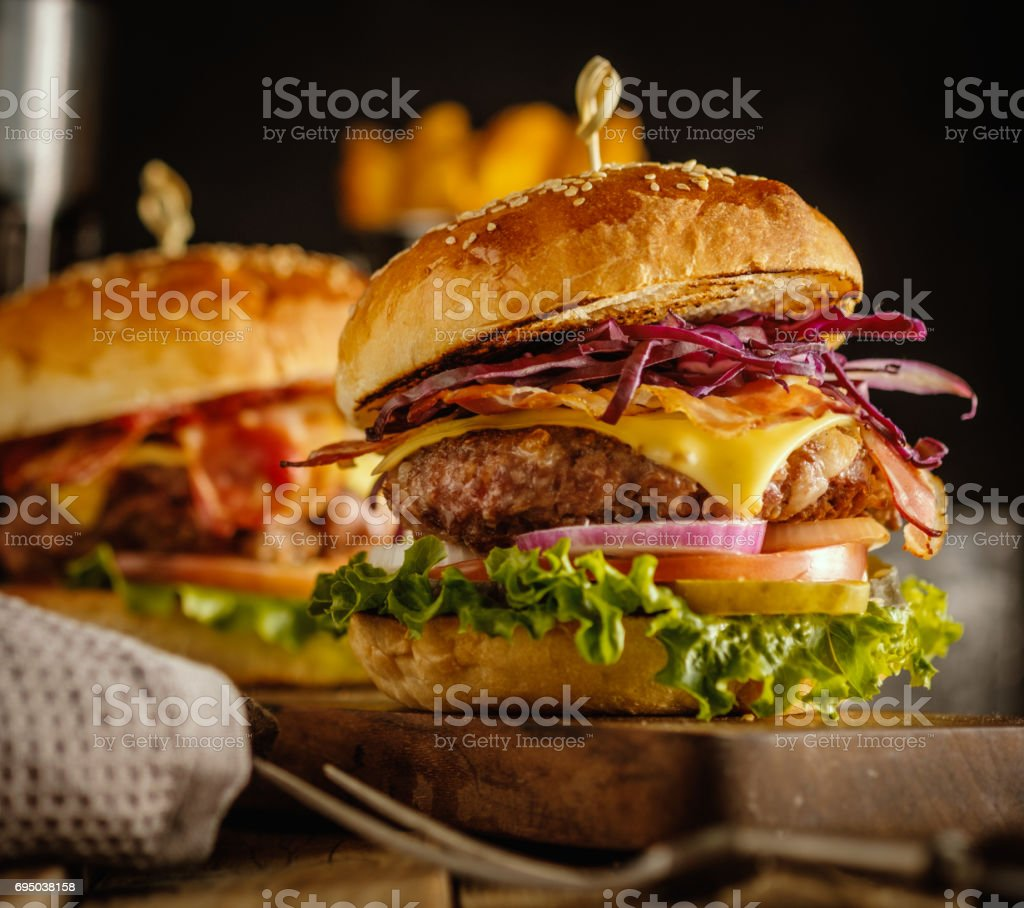 Delicious fresh burger with meat, bacon, cheese and vegetables on a wooden board, in a rustic soul style. стоковое фото