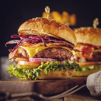 istock Delicious fresh burger with meat, bacon, cheese and vegetables on a wooden board, in a rustic soul style. 695044732