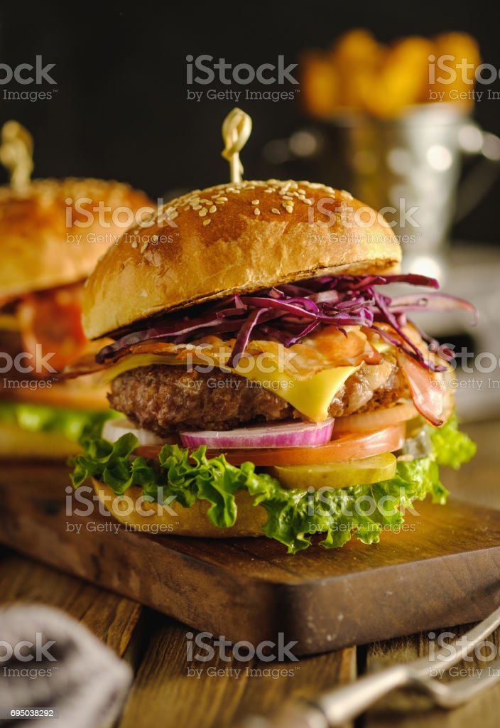 Delicious fresh hamburger with meat, cheese and vegetables on wooden board stock photo