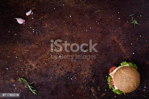istock Delicious fresh homemade burger on a rustic table. Menu frame. 671763216