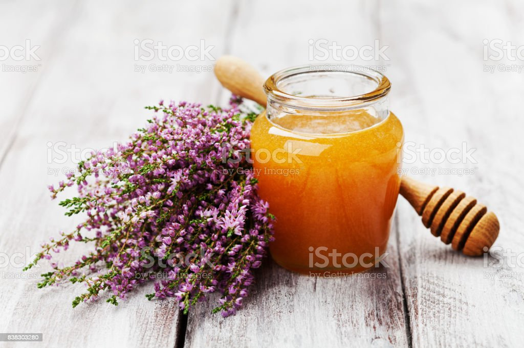 Delicious fresh honey in pot or jar and flowers heather on wooden vintage background. stock photo