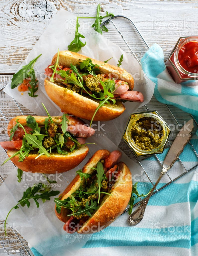 Delicious fresh hot dogs in homemade buns with arugula and ketchup on a wooden background. стоковое фото