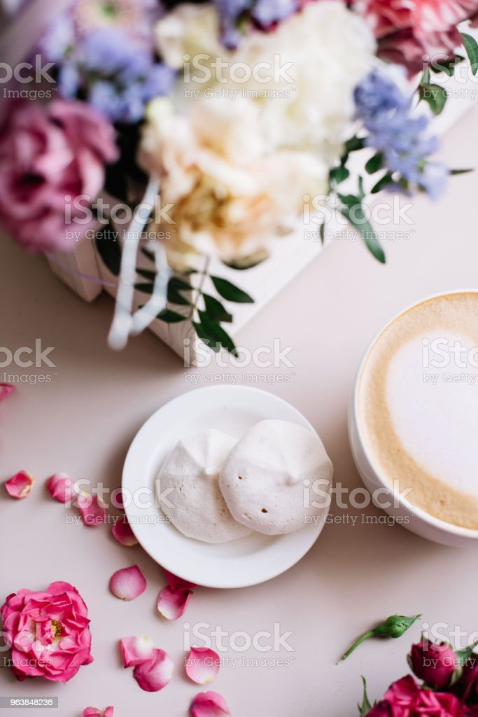 Delicious fresh morning cappuccino coffee with heart latte art on it, little white marshmallows and a basket of blossoming  flowers on the pastel pink background, top view, flat lay - Royalty-free Aura Stock Photo
