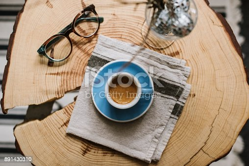 istock Delicious fresh morning espresso coffee with a breautiful crema in a blue demitasse cup with a saucer on the pine wood slab hand-made table with glasses and fancy decoration on it, flat lay 891430310