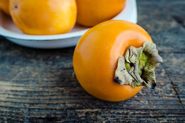 köstliche frische kaki früchte auf holztisch - sharonfrucht stock-fotos und bilder