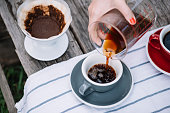 Delicious fresh pourover coffee pouring into the ceramic grey cup