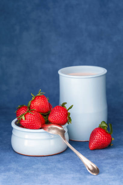 Delicious fresh strawberries in a bowl with yogurt and a spoon stock photo