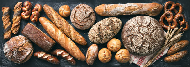Delicious freshly baked bread assortment on dark rustic background stock photo