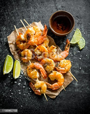Delicious freshly cooked shrimps on skewers. On dark rustic background