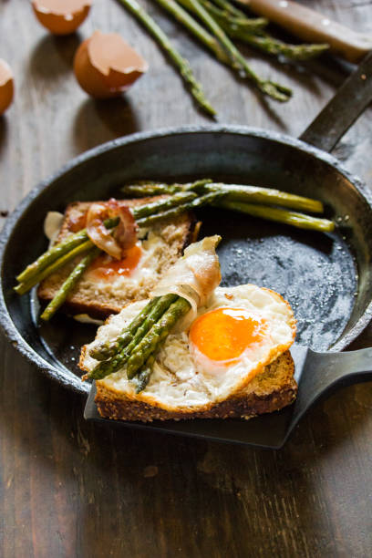 Delicious fried eggs on a toasted bread in a metal pan with grilled asparagus wrapped in fried bacon. stock photo