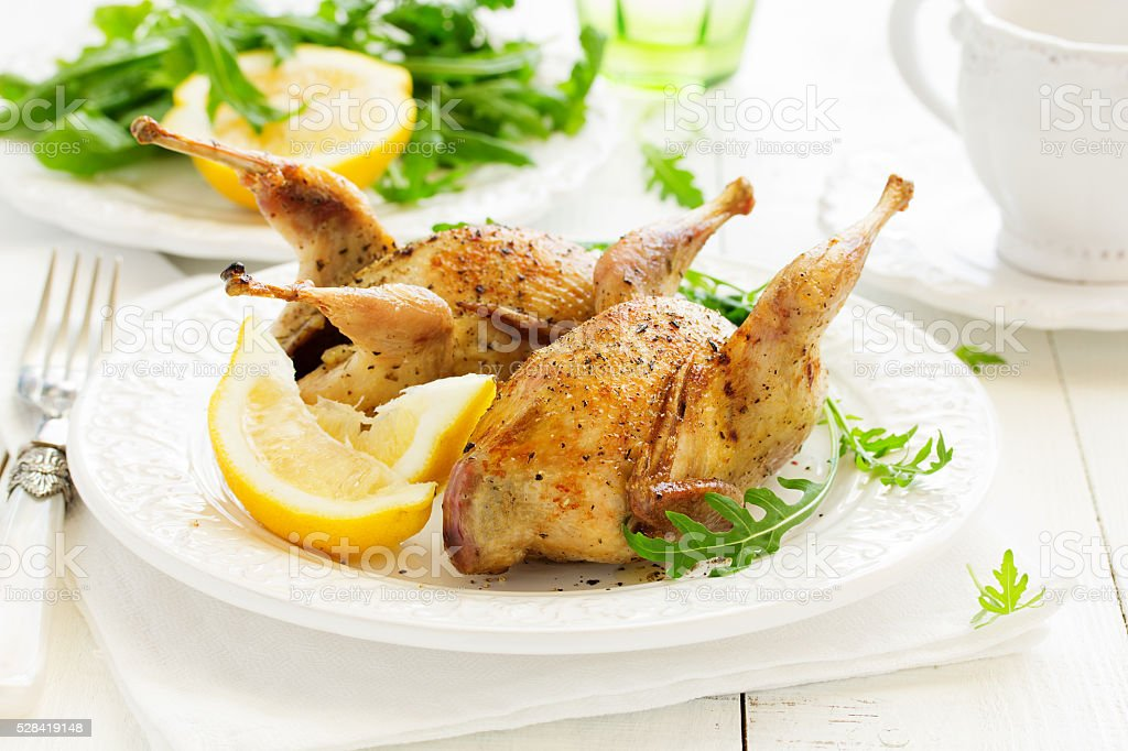 Delicious fried quail with herbs and greens. stock photo