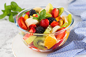 istock Delicious fruit salad on a plate on table. 1298307574