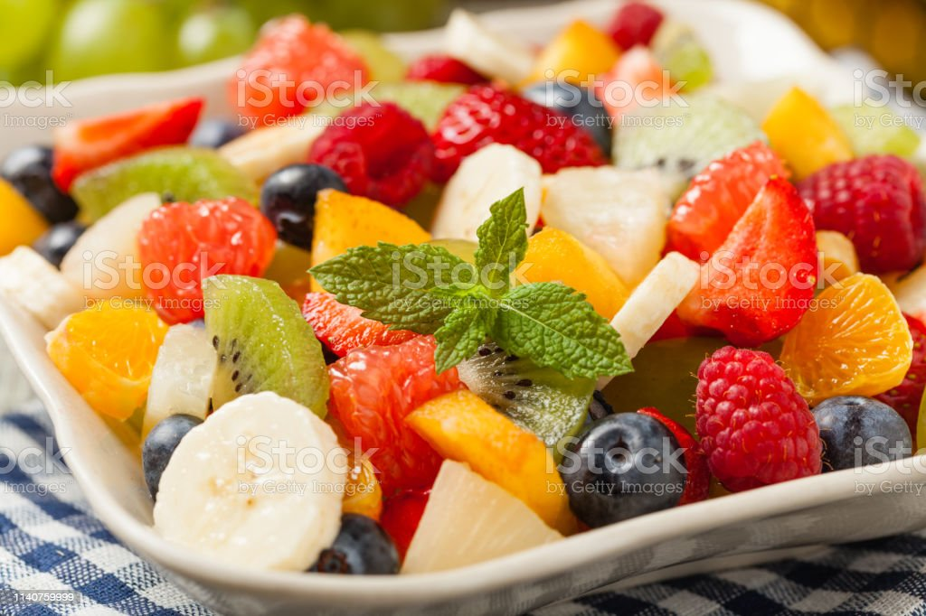 Delicious fruit salad with fresh fruit. Wooden, gray table in the...