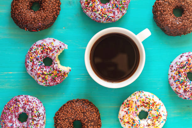 Delicious glazed donuts and cup of coffee on turquoise surface stock photo