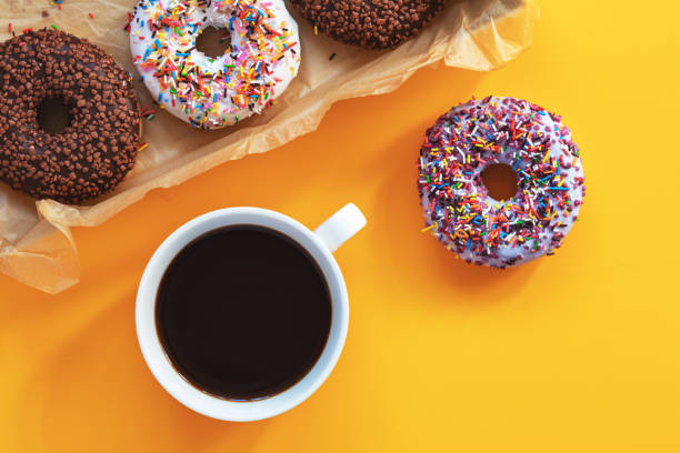 Delicious glazed donuts and cup of coffee on yellow surface stock photo