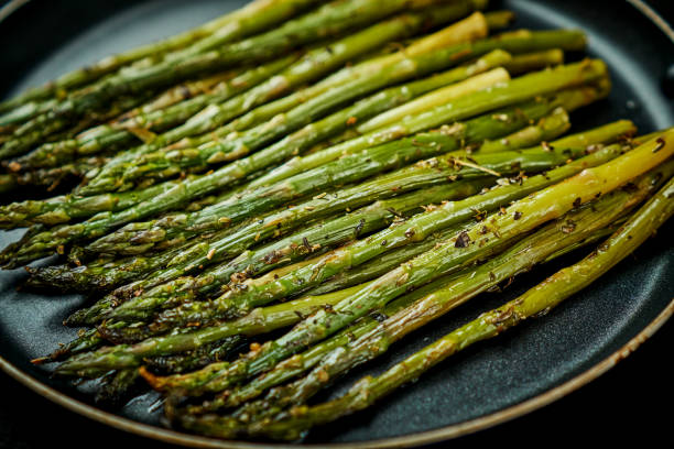 delicious green asparagus in a pan on an old wooden black table