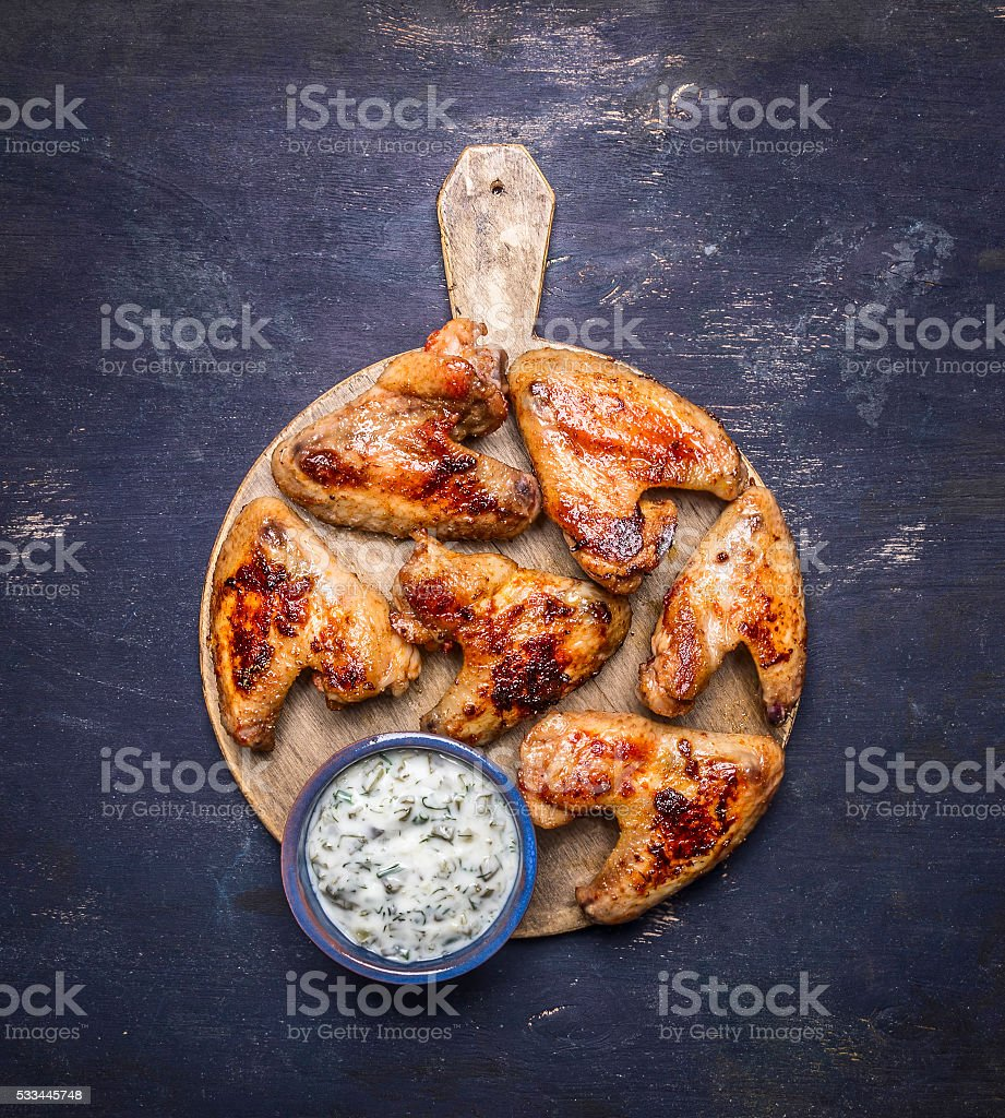 delicious grilled chicken wings garlic sauce cutting board top view stock photo
