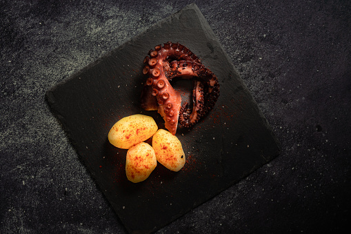 Delicious grilled octopus tentacles with potatoes seasoned with Spanish paprika, olive oil, and sea salt on a black slab and fancy background. Gourmet kitchen concept, culinary aesthetics.
