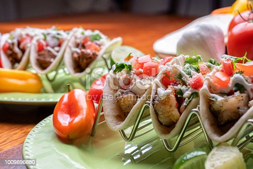 Grilled shrimp street food tacos with lime garnish, sour cream, cilantro and onion and cotija cheese