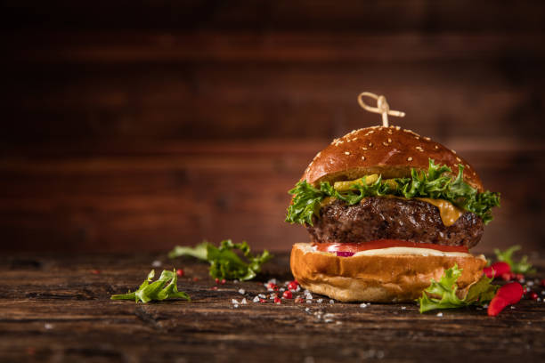 delicious hamburger, served on wood. - burgers stock pictures, royalty-free photos & images