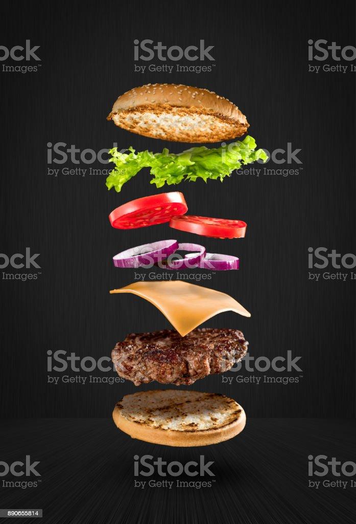 黒い背景に食材を飛んでの美味しいハンバーガー ストックフォト