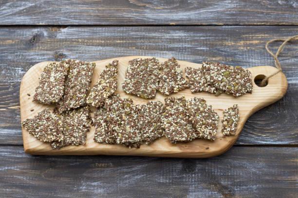 Köstliche gesunde Glutenfreie Knacker, ketogen, aus Chia-Samen, Lein, Sesam und gemahlenen Kürbiskernen auf einem Holztisch – Foto