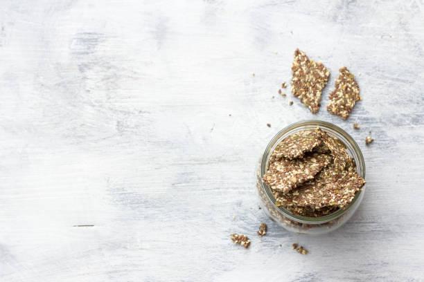 Köstliche gesunde Glutenfreie Knacker, ketogen, aus Chia-Samen, Lein, Sesam und gemahlenen Kürbiskernen in einem Glas auf grauem Hintergrund – Foto