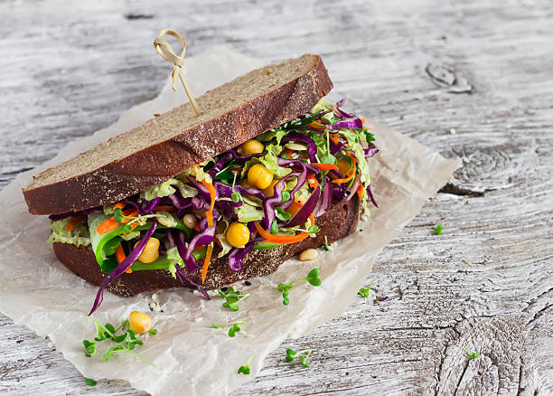 Delicious healthy vegetarian open cole slaw and a chickpea sandwich Delicious healthy vegetarian open cole slaw and a chickpea sandwich. On  light wooden rustic background microgreen stock pictures, royalty-free photos & images